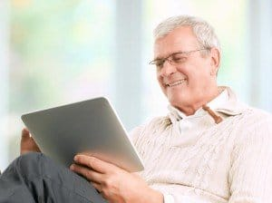 Senior working on digital tablet